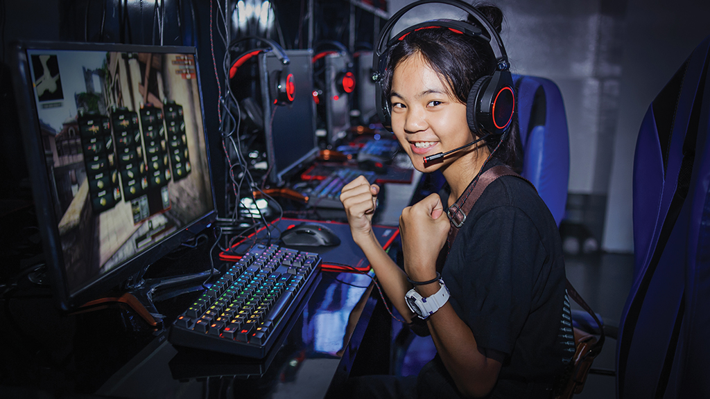 A girl in front of a computer wearing a headset gives a thumbs up to the camera