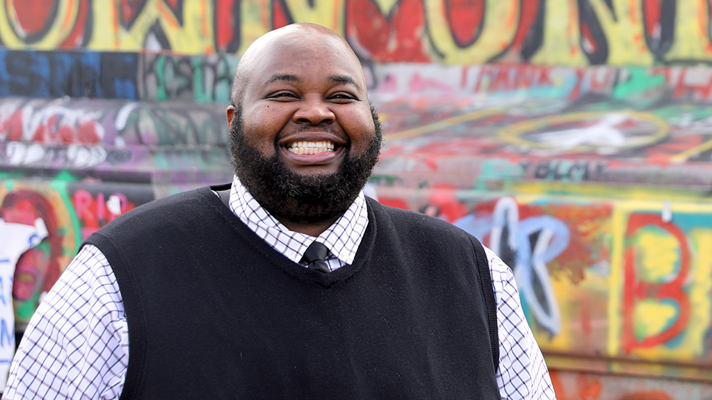 teacher of the year rodney robinson smiles brightly in front of a graffitied statue