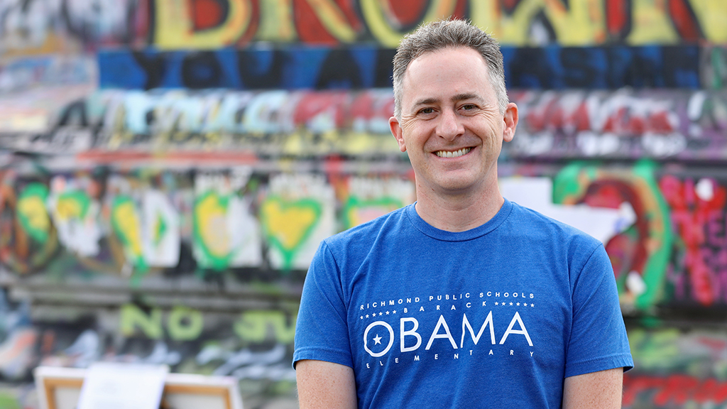 Jason Kamras smiles in front of a graffitied statue