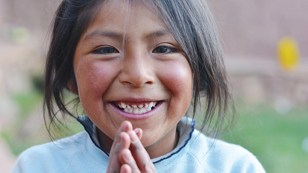 a native american girl with her hands clasped together smiles
