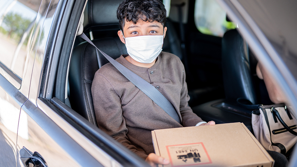 a student with a face mask in a car holds his new remote learning equipment