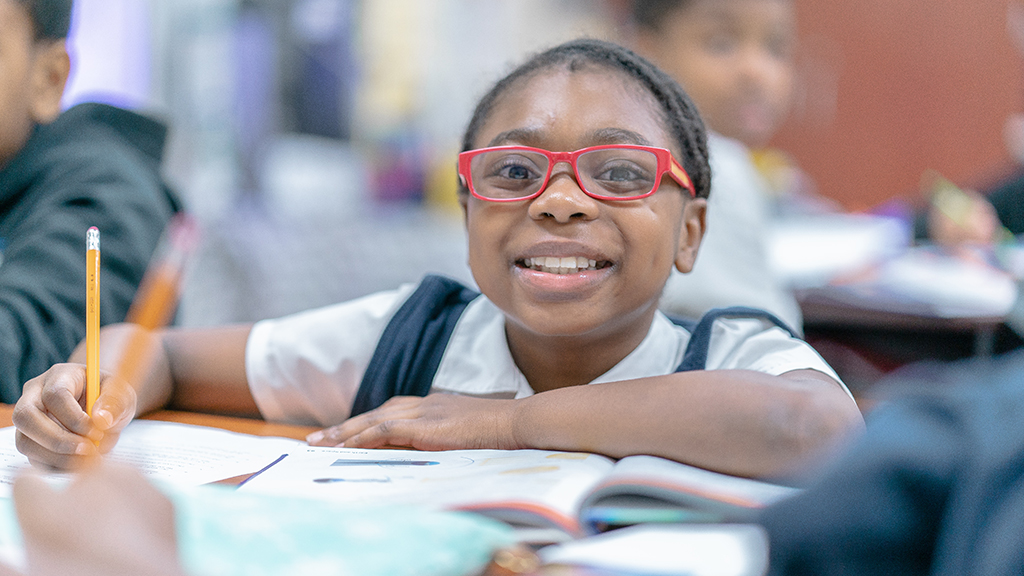 a student with big red glasses smiles brightly at the camera as she works at her desk