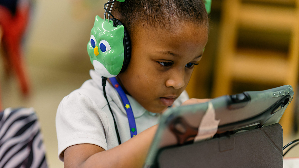 a child wearing owl headphones uses a digital device as part of a literacy program
