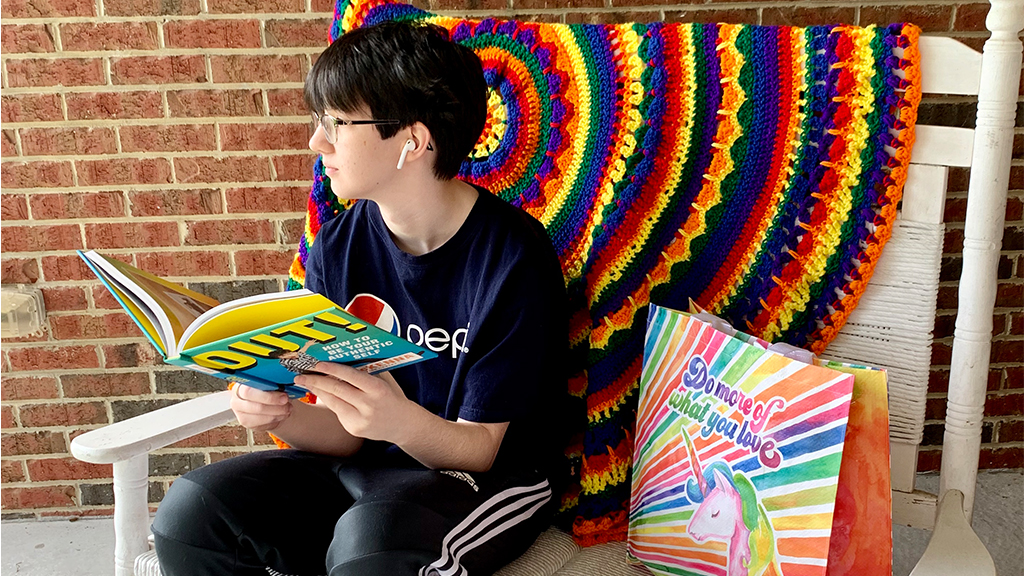 "a student sits on a chair with a rainbow blanket and reads a book entitled ""out!"""