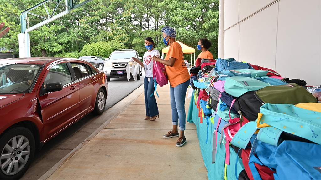 a large row of backpacks are being handed out by volunteers to cars in a drive thru