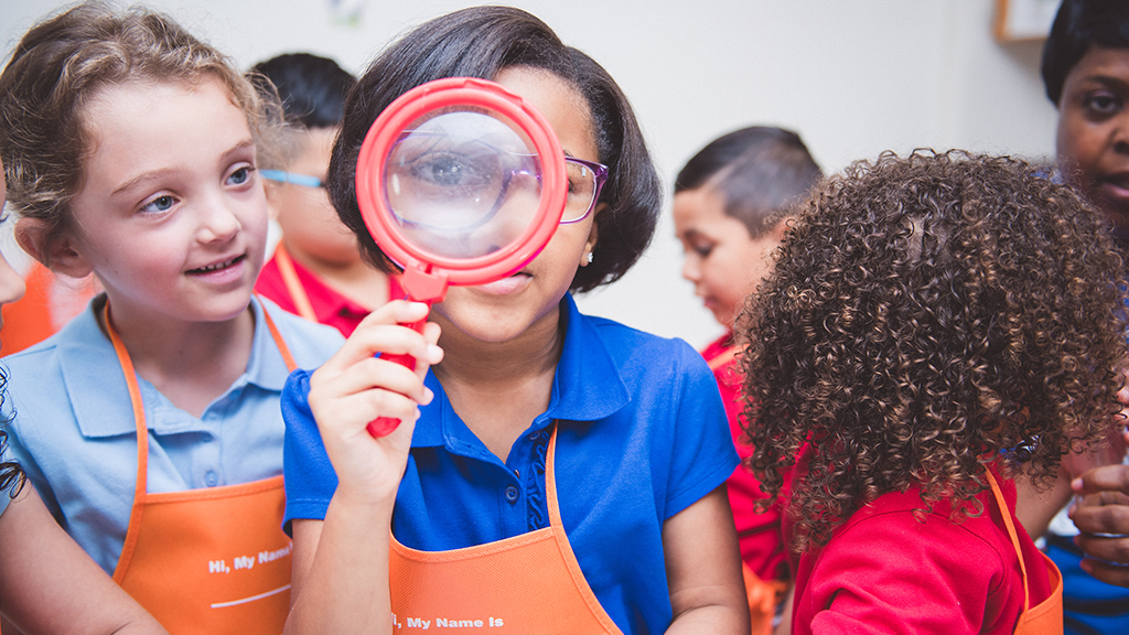 a student, surrounded by her classmates, looks through a magnifying glass