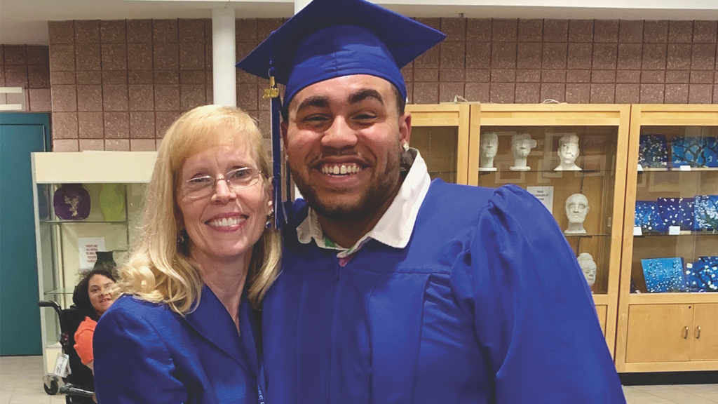 the superintendent of the district embraces a student on graduation day, they are both in academic regalia and the student is wearing a graduation cap
