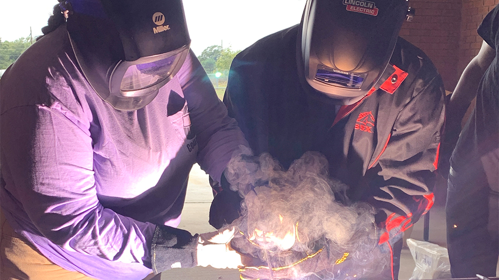 two students wearing protective clothes use wielding equipment, producing a cloud of steam and light