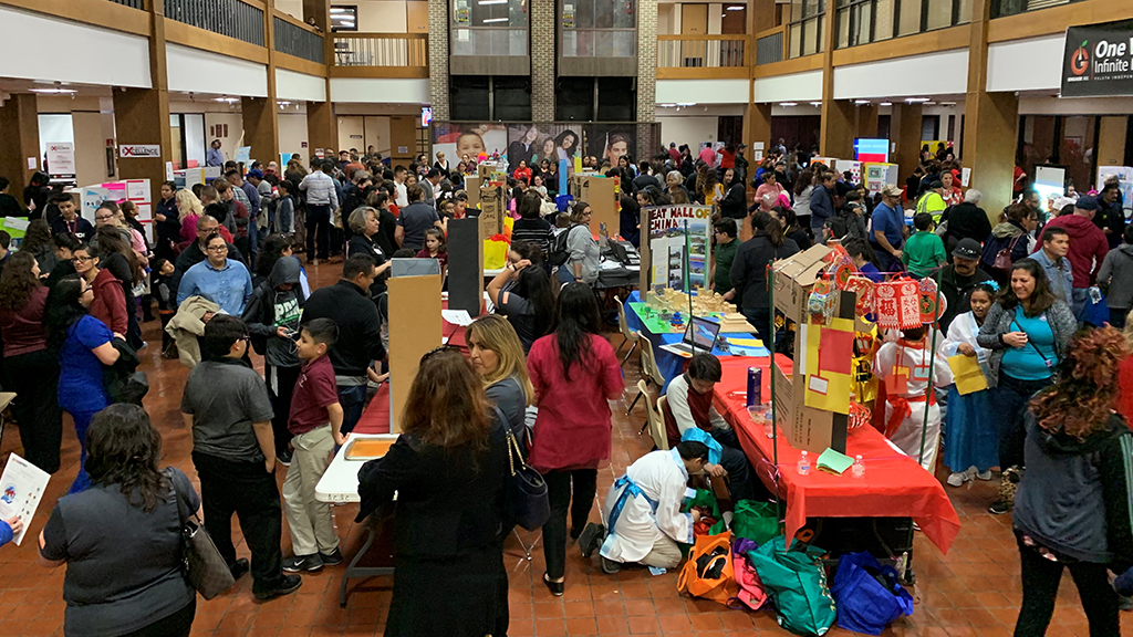 a crowd of people walk through a large room that has been set up to display projects at each table