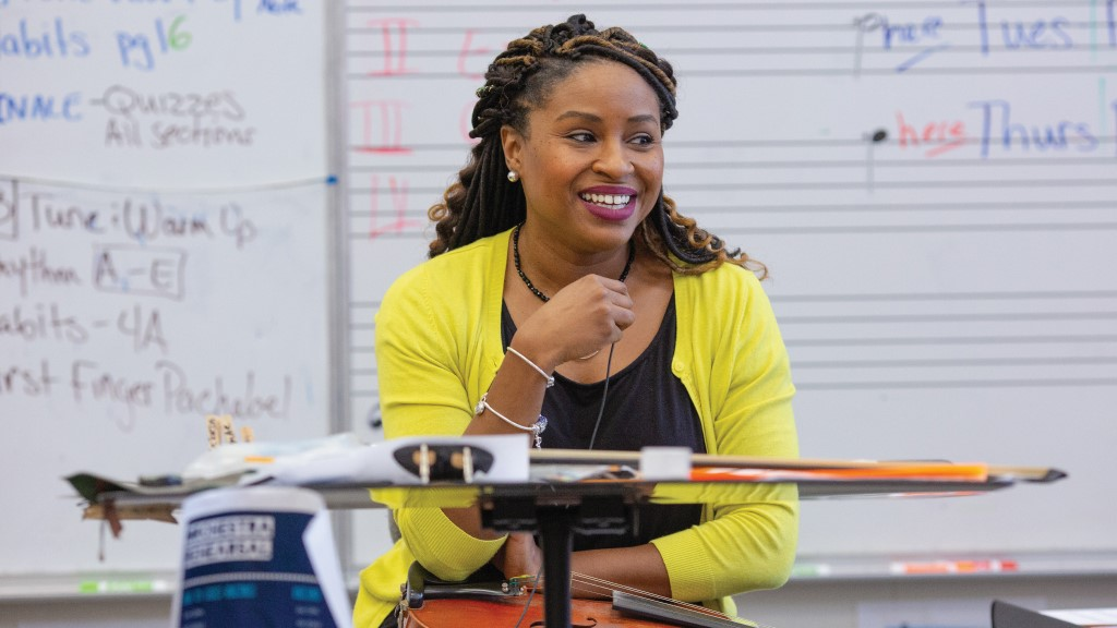 a black female music teacher smiles at her students out of frame