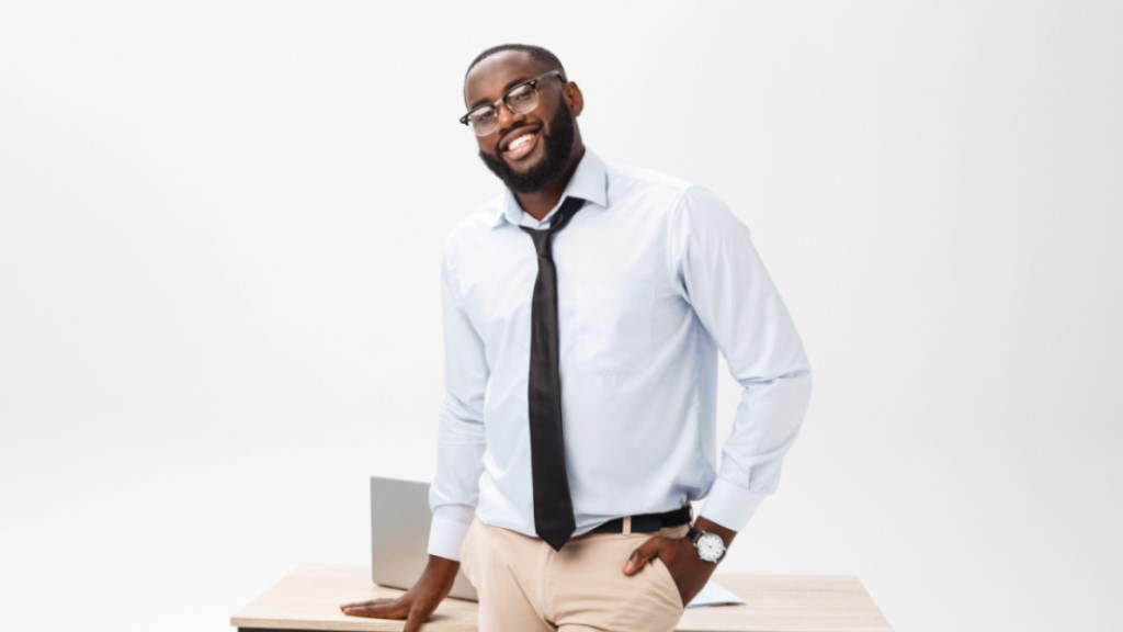 a black male teacher stands near his desk and smiles at the camera