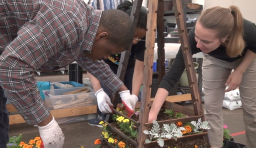 Two students work on a garden structure together