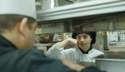 A student in a chef hat communicates with another kitchen worker