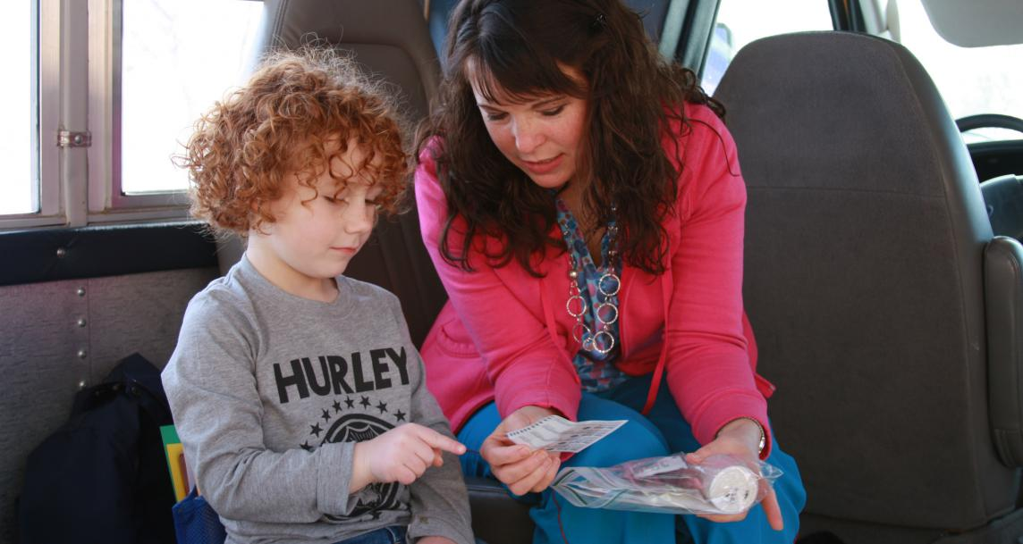A child and an adult review paper on a bus